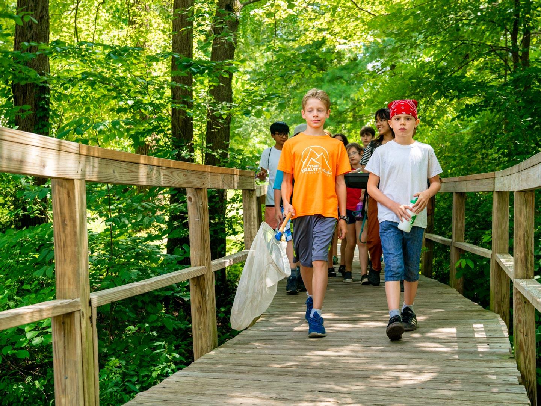 campers walking a bridge in the woods