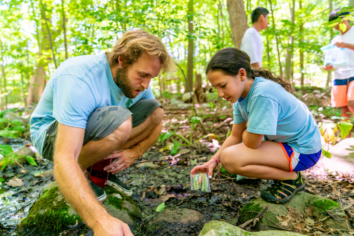 Camper learning skills from a counselor