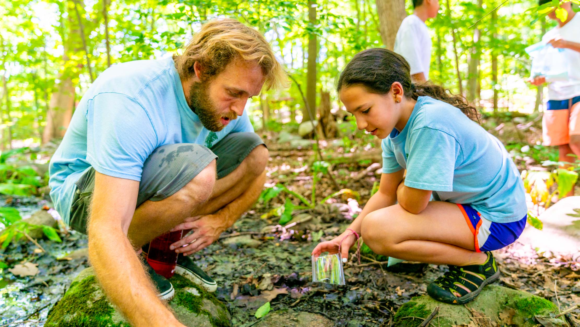 Camper and counselor examining the dirt