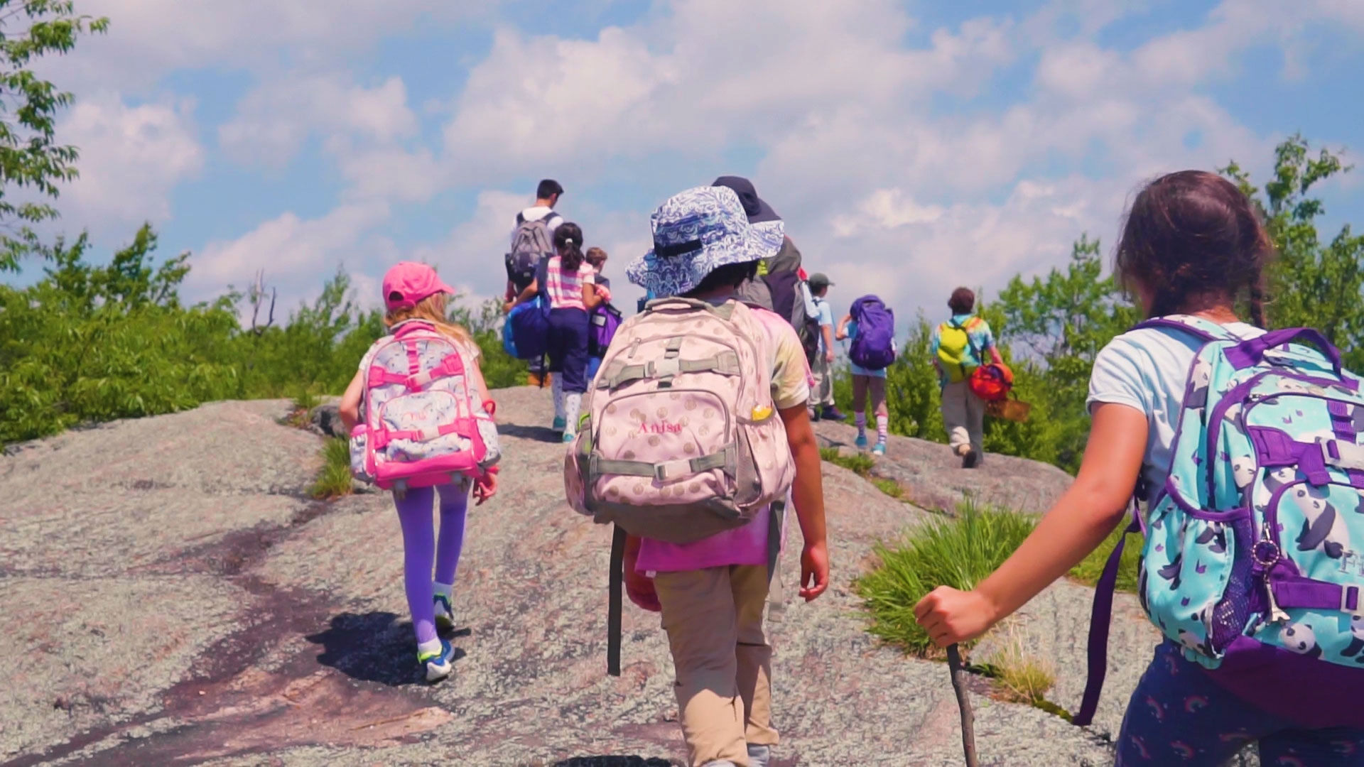 Campers hiking up a hill with full backpacks