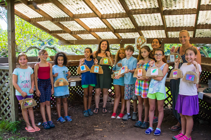 Campers holding up their art with the instructor Shaina