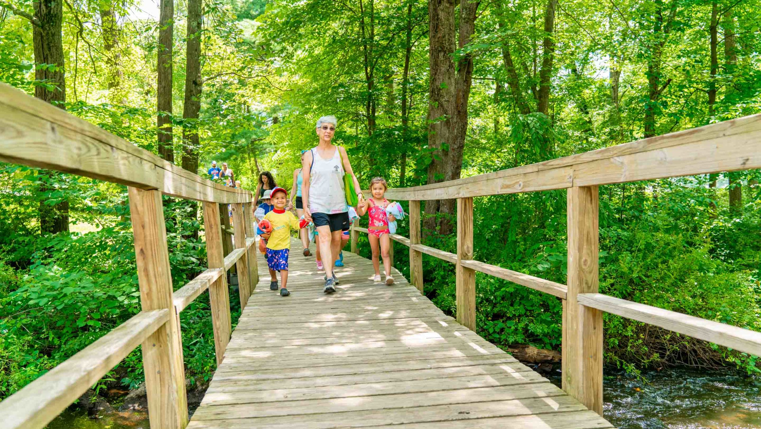 Counselor walking with young campers over a bridge in the woods