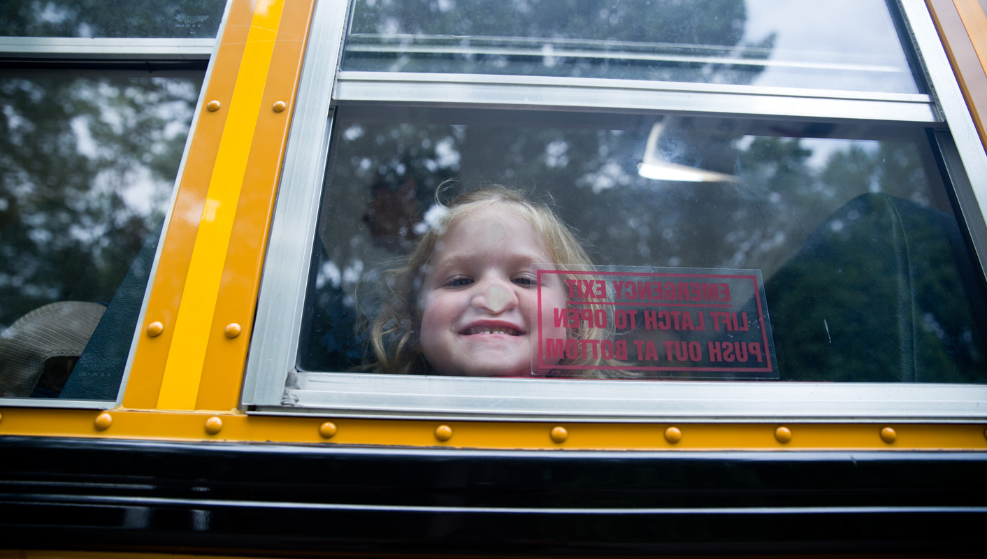 Campers pressing her nose against the bus window
