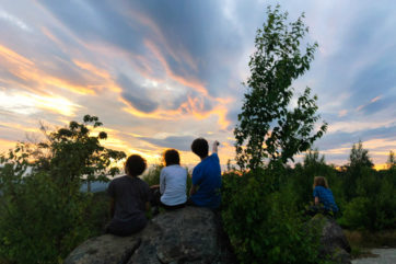Campers sitting on a rock looking at the sun set