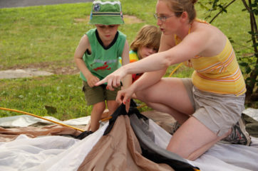 Young campers learning how to put up a tent