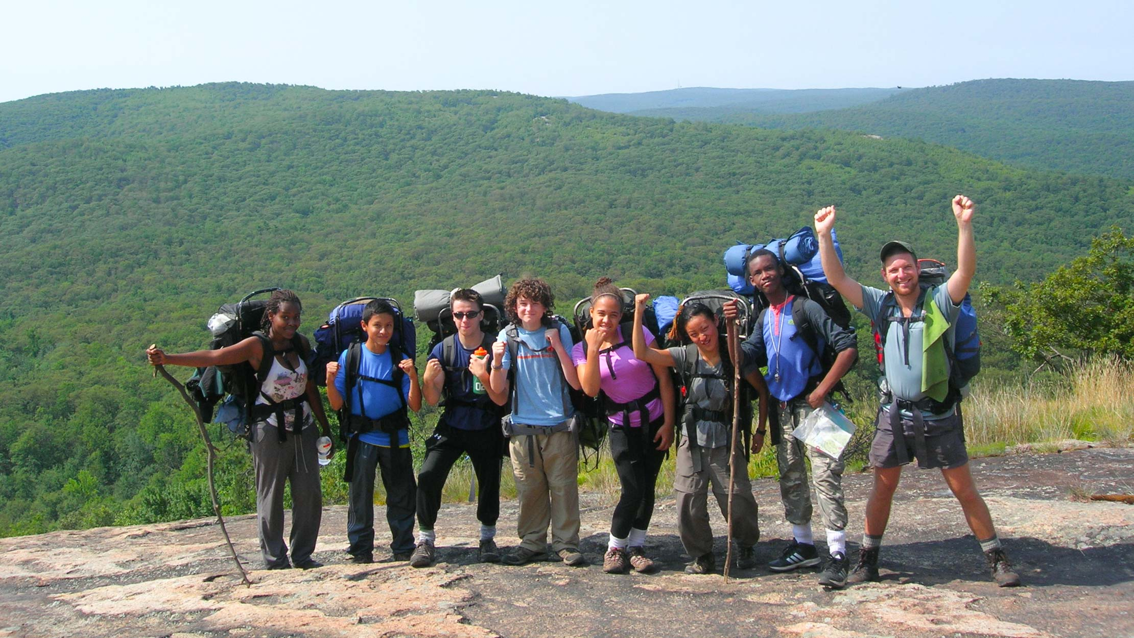 Campers on a camping trip taking a group photo with their backpacks on