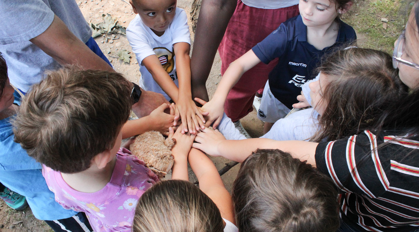 Campers putting their hands in the circle for a group chant