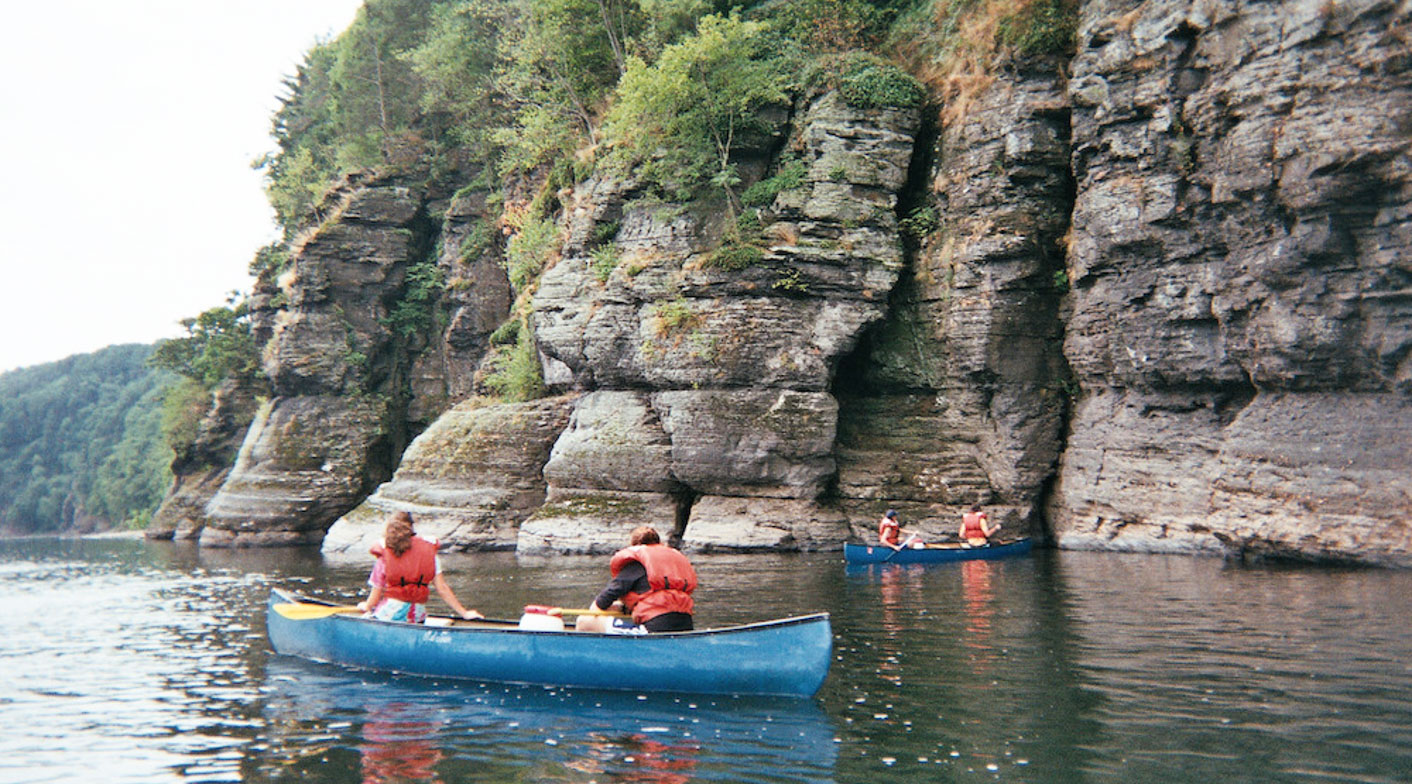 Campers in canoes by a cliff