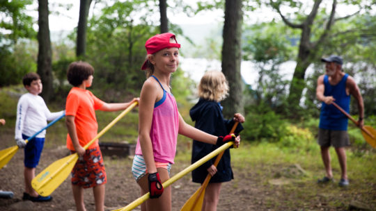 Campers practicing paddle techniques with canoe paddles