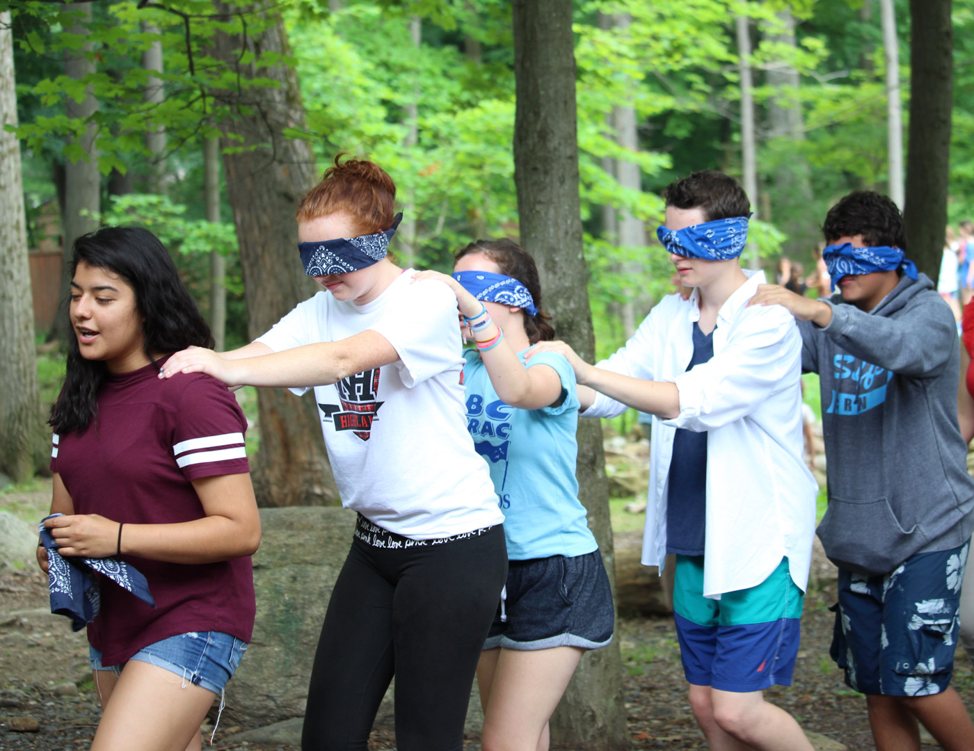Campers participating in a group bonding exercise with blindfolds all walking in a line with hands on the shoulders of the person in front of them