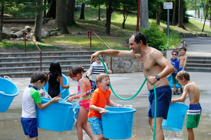 Counselor spraying campers with a hose