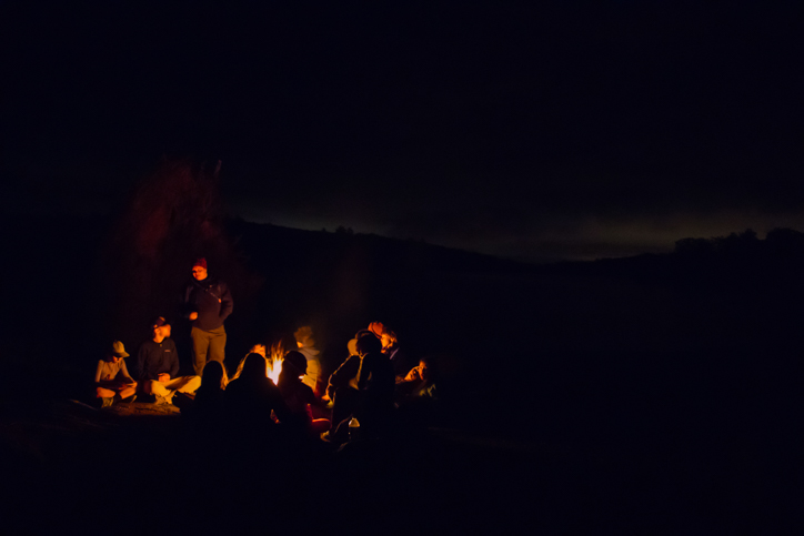 Campers gathered around a campfire at night