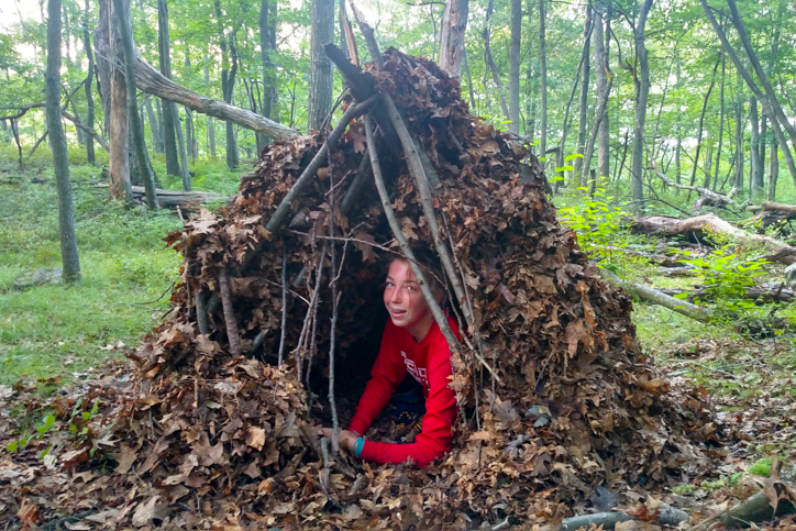 Camper in a fort built of leaves and branches