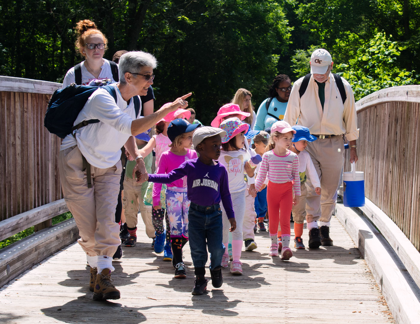 Young campers walking with counselors over a bridge on a day hike