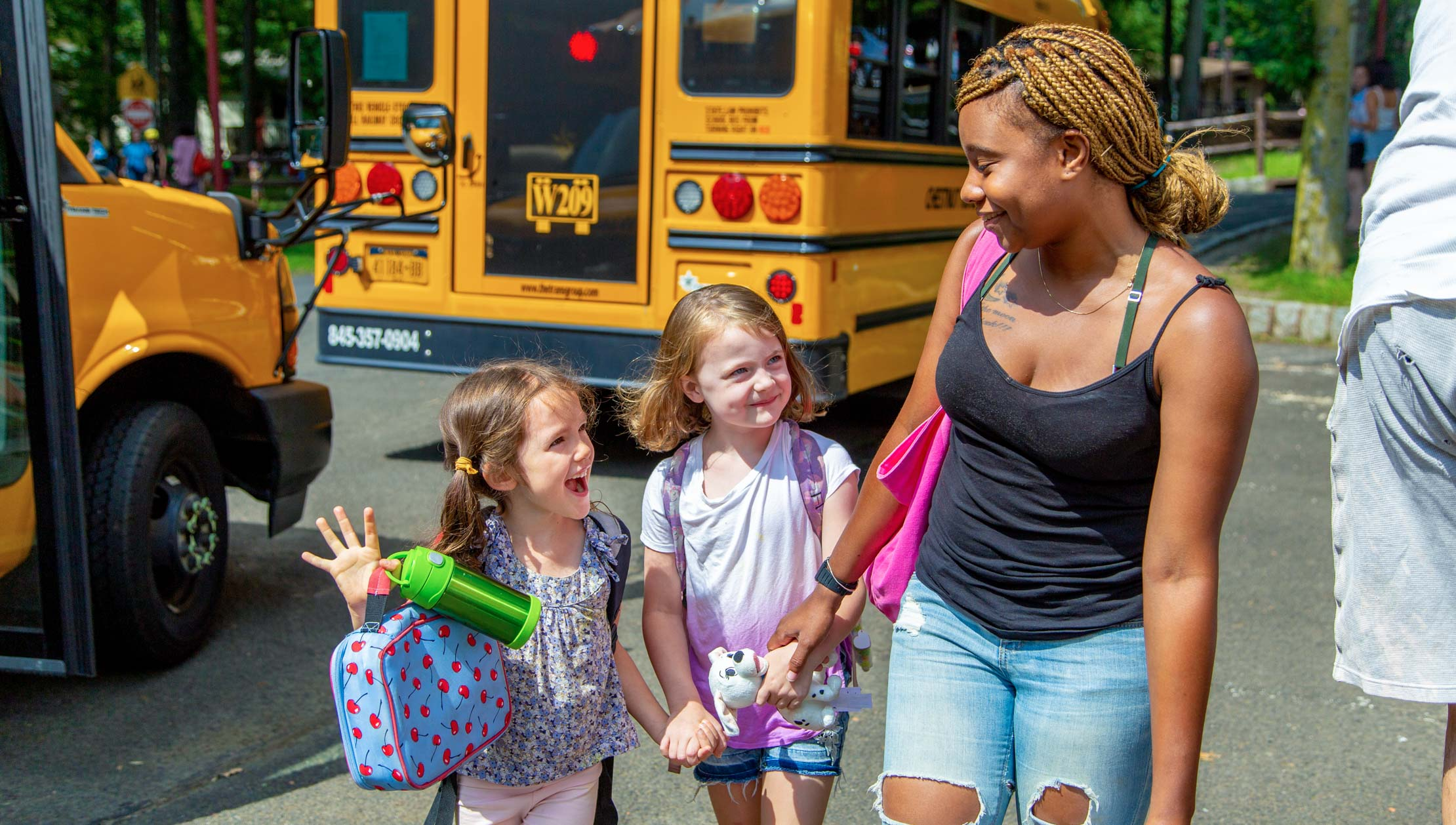 Campers walking with counselor from the bus