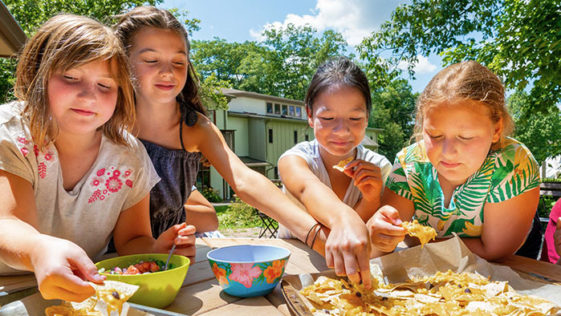 A group of girls gathered around a table enjoy a plate of nachos.
